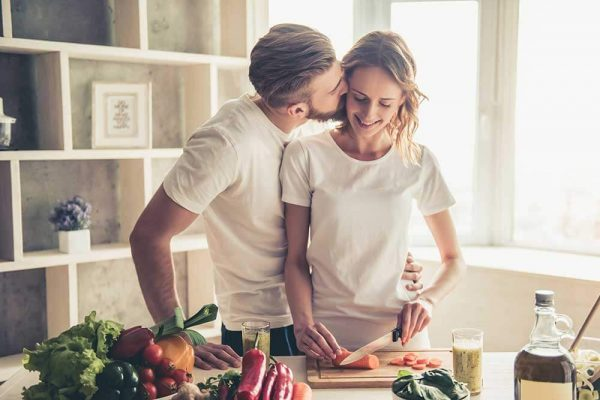 happy young couple cooking healthy food